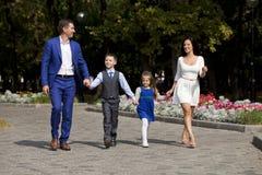 Счастливая семья идя вдоль пригородной улицы Стоковые Изображения RF