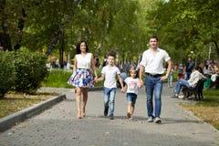 Счастливая семья идя вдоль пригородной улицы Стоковое фото RF