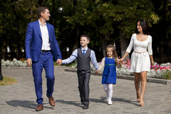 Счастливая семья идя вдоль пригородной улицы Стоковые Изображения