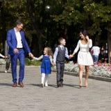 Счастливая семья идя вдоль пригородной улицы Стоковая Фотография RF