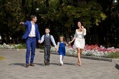 Счастливая семья идя вдоль пригородной улицы Стоковое Изображение