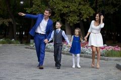 Счастливая семья идя вдоль пригородной улицы Стоковая Фотография
