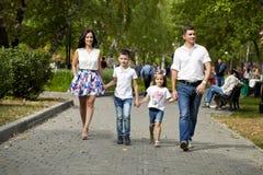 Счастливая семья идя вдоль пригородной улицы Стоковое Фото