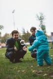 Счастливая семья идя в парк осени: мать, отец и их маленький сын - выучите погулять независимо Стоковые Фото
