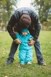 Счастливая семья идя в парк осени: отец и его маленький сын - выучите стоять независимо Стоковые Фотографии RF