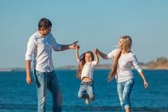 Счастливая семья которая играя на пляже Концепция  Стоковые Фотографии RF