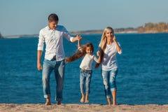 Счастливая семья которая играя на пляже Концепция  Стоковая Фотография RF