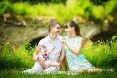 Счастливая семья, мама, папа и маленький сын имея потеху в парке Su стоковое изображение rf