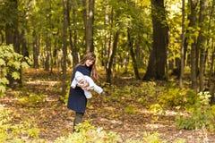 Счастливая семья, материнство и концепция младенца Усмехаясь мать и маленькая дочь играя совместно в парке Стоковые Фотографии RF
