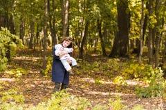 Счастливая семья, материнство и концепция младенца Усмехаясь мать и маленькая дочь играя совместно в парке Стоковые Фото
