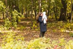 Счастливая семья, материнство и концепция младенца Усмехаясь мать и маленькая дочь играя совместно в парке Стоковое фото RF