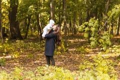 Счастливая семья, материнство и концепция младенца Усмехаясь мать и маленькая дочь играя совместно в парке Стоковое Изображение RF