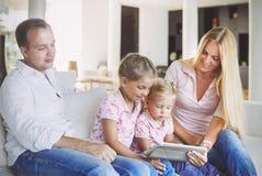 Счастливая семья матери, отца и дочерей сидя на софе a Стоковая Фотография
