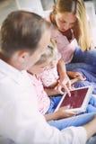 Счастливая семья матери, отца и дочерей сидя на софе a Стоковые Фото