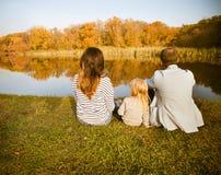 Счастливая семья - мать, отец и дочери ослабляя на осени c стоковые фото