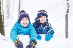 Счастливая семья: 2 маленьких двойных мальчика имея потеху с снегом в winte Стоковая Фотография
