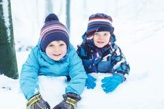 Счастливая семья: 2 маленьких двойных мальчика имея потеху с снегом в winte Стоковые Фотографии RF