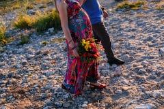 Счастливая семья: молодая красивая беременная женщина, человек идя вдоль камней моря на летний день Sunnset стоковая фотография