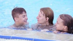 Счастливая семья наслаждаясь в бассейне сток-видео