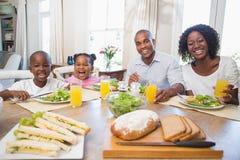 Счастливая семья наслаждаясь здоровой едой совместно стоковое изображение
