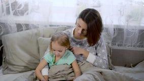 Счастливая семья наслаждаясь одином другого во времени ложиться спать Довольно молодая мать читает книгу к ее маленькой милой доч акции видеоматериалы