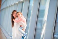 Счастливая семья на авиапорте сидя на чемодане с восхождением на борт посадочного талона ждать Стоковая Фотография RF