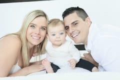 Счастливая семья на белой кровати в спальне Стоковые Изображения RF