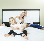 Счастливая семья на белой кровати в спальне Стоковые Фотографии RF