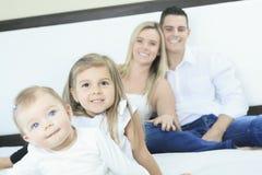 Счастливая семья на белой кровати в спальне Стоковое Фото