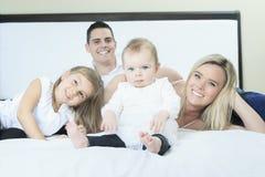 Счастливая семья на белой кровати в спальне Стоковое фото RF