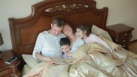Счастливая семья на кровати читая книгу вне громко дома акции видеоматериалы