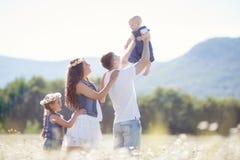 Счастливая семья на поле зацветая маргариток Стоковое Изображение