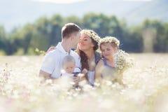Счастливая семья на поле зацветая маргариток Стоковые Фотографии RF