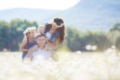 Счастливая семья на поле зацветая маргариток Стоковые Изображения RF