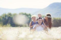 Счастливая семья на поле зацветая маргариток Стоковое Фото