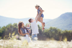 Счастливая семья на поле зацветая маргариток Стоковые Изображения