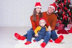 Счастливая семья на Рожденственской ночи сидя совместно около украшенного дерева Стоковое Изображение RF