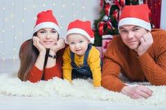 Счастливая семья на Рожденственской ночи сидя совместно около украшенного дерева Стоковые Изображения RF