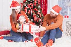 Счастливая семья на Рожденственской ночи сидя совместно около украшенного дерева Стоковые Фотографии RF