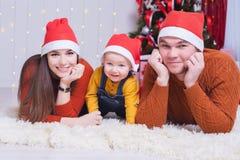 Счастливая семья на Рожденственской ночи сидя совместно около украшенного дерева Стоковые Фото
