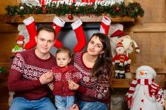 Счастливая семья около камина на рождестве Стоковое Фото