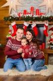 Счастливая семья около камина на рождестве Стоковые Фотографии RF