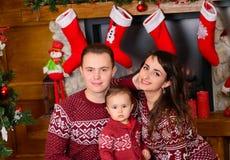 Счастливая семья около камина на рождестве Стоковые Изображения RF