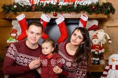Счастливая семья около камина на рождестве Стоковая Фотография