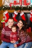 Счастливая семья около камина на рождестве Стоковая Фотография RF