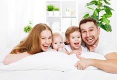 Счастливая семья дома в кровати Стоковое Фото