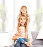 Счастливая семья дома на кресле. Мать и дочь и сын Стоковое фото RF