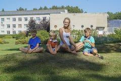 Счастливая семья ослабляя на зеленой траве Стоковые Фотографии RF
