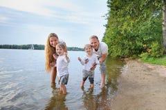 Счастливая семья - отец, мать, 2 сыновь на пляже с их ногами в воде на заходе солнца Стоковое фото RF