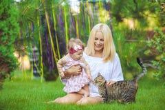 Счастливая семья отдыхая в парке зеленого цвета лета Стоковое Изображение
